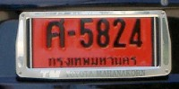 temporary dealer issued license plates for car black letters and 1 2 3 or 4 black digits on a red background driving with this type of licence